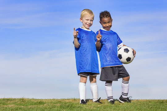 Two diverse young soccer players showing No. 1 sign. Full length view of two youth recreation league soccer players