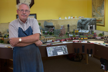 Happy Retired Man working on a large model in his workshop.