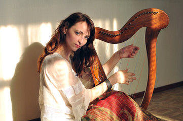 Woman plays celtic harp in folk style