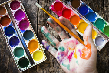 watercolor paint brush to paint the hand of the artist in multi-colored paint on wood background holding a brush