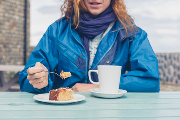 Woman having coffee and cake at table outside