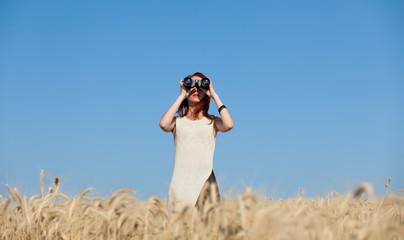 girl with binocular at wheat field.