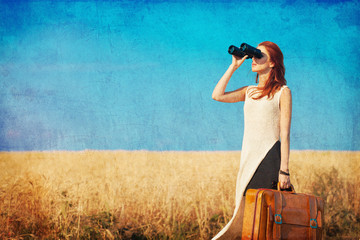 girl with suitcase and binocular at countryside road