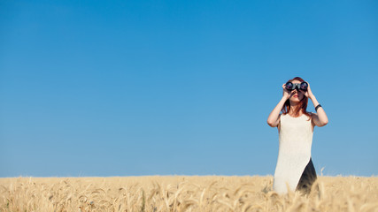 girl with binocular at wheat field.
