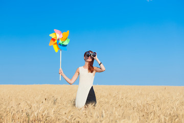 girl in white dress with binocular and wind toy