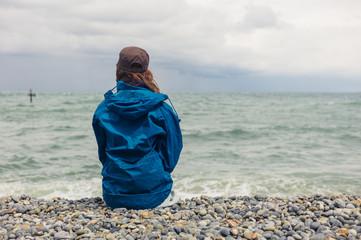 Woman in blue jacket sitting on beach