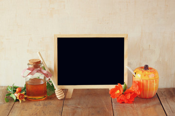 rosh hashanah (jewesh holiday) concept - blackboard, honey