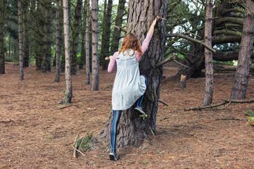 Young woman climbing a tree