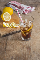 Glass of cola with lemons on a wooden table