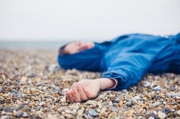 Unconscious woman on shingle beach