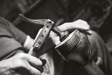 old artisian shoemaker hit shoes with hammer