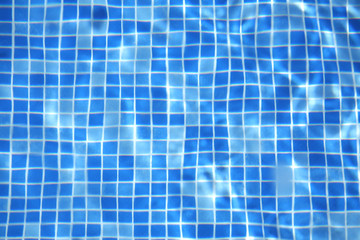 Sun reflected in the swimming pool water as a background