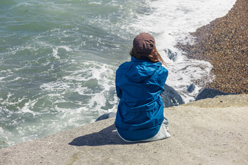 Woman sitting on flood defense by the sea