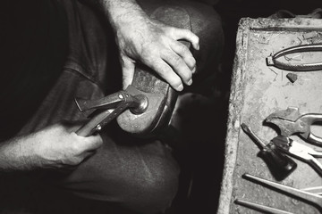old shoemaker hit shoes with hammer in his workshop