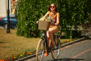 Pretty young woman with bicycle in the park