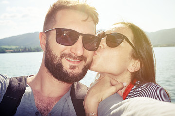 kissing couple taking selfie