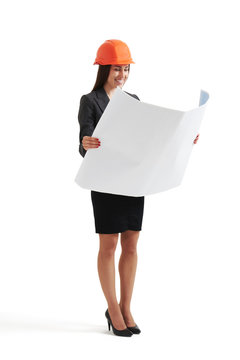 woman in hardhat looking at blueprint