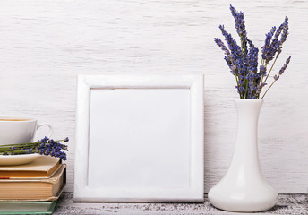White colored interior, vase with lavender flowers and books