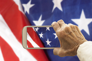 Old hand takes a picture of USA flag, on smart phone.