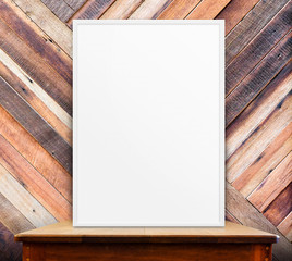 Empty white frame on wooden table at tropical diagonal wood wall