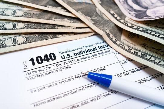 1040 individual tax return form and american dollar bills money closeup