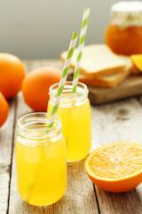 Orange juice in bottle on grey wooden background