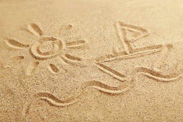 Drawing sun and ship on beach sand