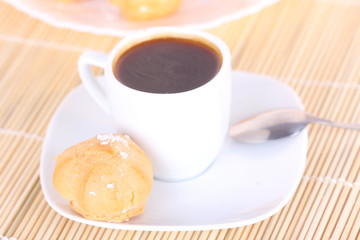Cup of coffee and cake on wooden mat