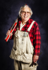 Portrait of an old happy carpenter on a canvas background.