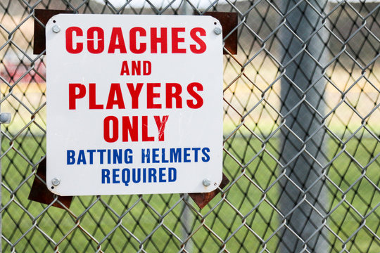 Sign on a batting cage that says it is for coaches and players only and that batting helmets are required