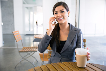 Chatty business woman executive on a break networking on phone at a coffee shop