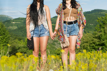 Two young hippie women holding hands