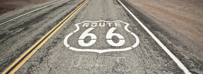 Route 66 pavement sign sunrise in California's Mojave desert.