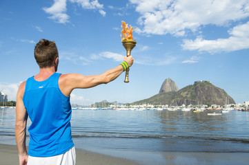 Athlete holding sport torch against Rio de Janeiro Brazil skyline with Sugarloaf Mountain