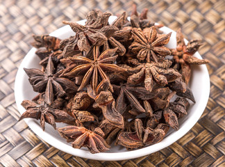 Star anise spice in white bowl over wicker background