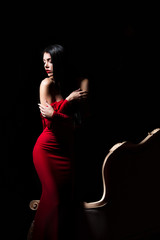 Elegant woman in red dress in darkness. Female in dramatic