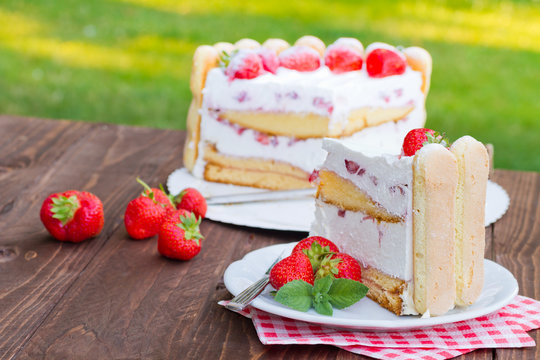 Slice of strawberry cake Charlotte served on a plate. Ladyfingers built around a creamy mousse center with layers of fresh berries. Luxury light summer cake
