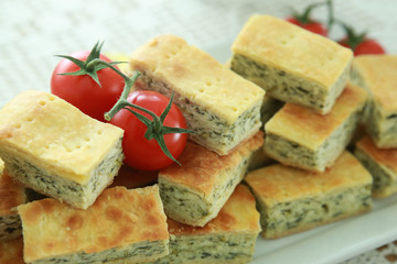 Homemade Ricotta cheese and spinach pie slice with tomato