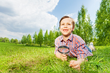 Happy boy holds magnifier lays on the green grass