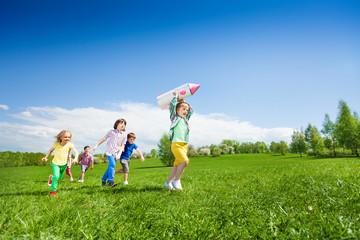 Children run after boy holding rocket carton toy