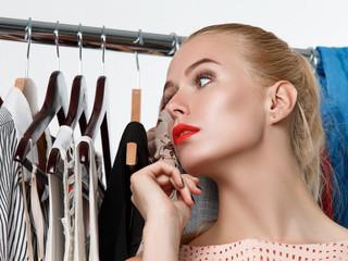 Beautiful blonde woman standing near wardrobe rack