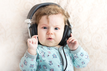 Funny baby in a big headphones. Portrait of a little boy. Cute child.