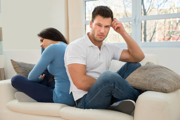 Displeased Couple Sitting On Couch After Quarrel