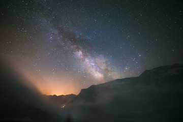 Idyllic Milky Way with clouds and fog in the Alps