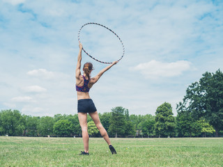Woman standing in park with hula hoop