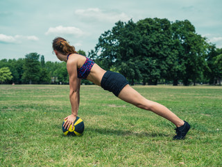 Woman exercising in park with medicine ball