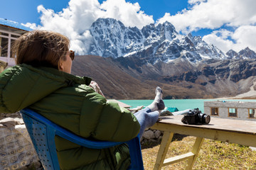 Wall Mural - Young woman tourist sitting resting infront mountains ridge view