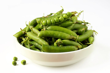 green peas in a white bowl on a white background