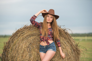 Beautiful woman wearing cowboy style near haystack