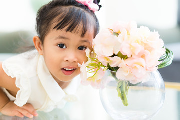 Adorable little girl take photo with flower